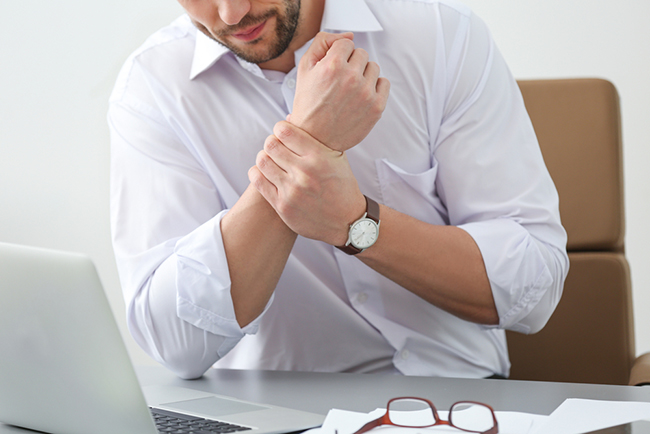 Man holding wrist in pain